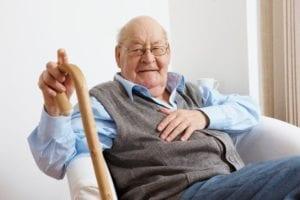 An elderly man sitting down with a walking stick